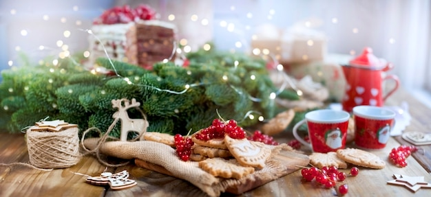 Two small cups of coffee and a coffee pot, a cake with berries and cookies, gifts, near a christmas tree on a village table near the window Premium Photo