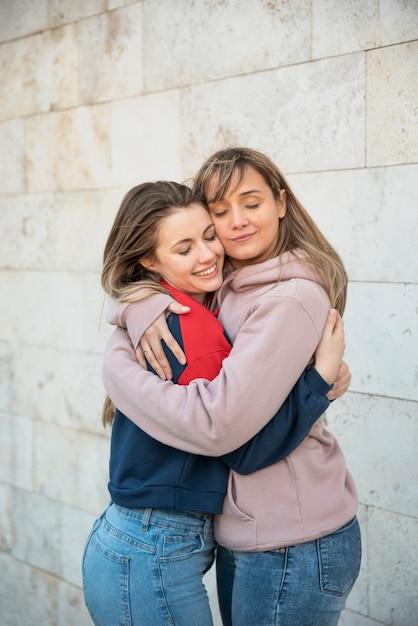 Две улыбающиеся молодые женщины обнимаются Бесплатные Фотографии