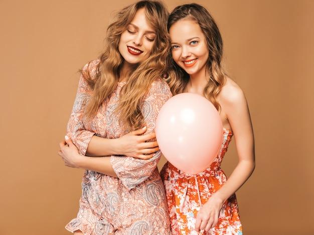 여름 드레스에 두 웃는 아름 다운 여자. 포즈를 취하는 여자. 다채로운 풍선과 함께 모델입니다. 즐거운 생일 축하 파티를위한 준비 무료 사진