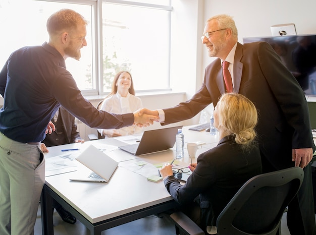 Two smiling businessman shaking hands together in the board meeting Free Photo