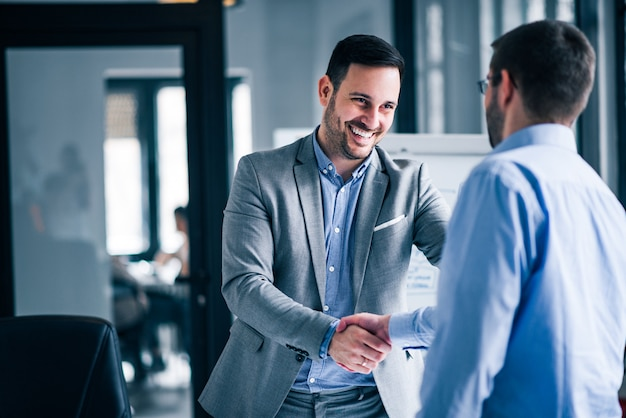 Two smiling businessmen shaking hands while standing in an office. Premium Photo