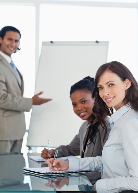 Two smiling executives working during a presentation while writing in a notebook Premium Photo