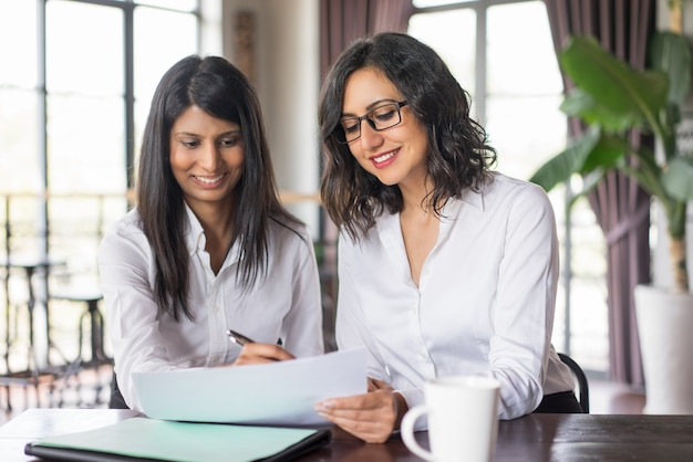 Two smiling female coworkers planning in cafe. Free Photo