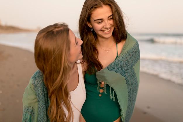 Two smiling female friends enjoying at beach Free Photo