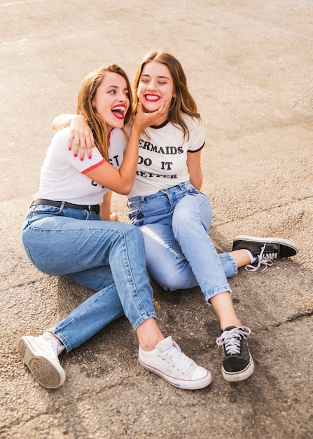 Two smiling female friends sitting on pavement Free Photo