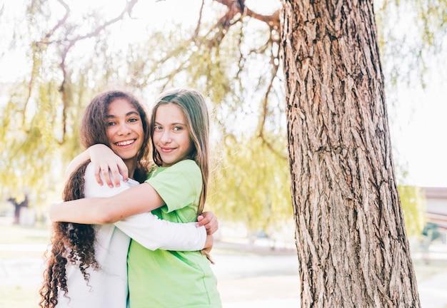 Две улыбающиеся подруги обнимаются под елкой Бесплатные Фотографии