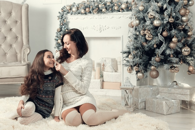 Two smiling girls, mother and daughter siting on a floor in christmas decorated room. Premium Photo
