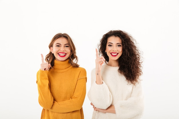 Two smiling girls in sweaters pointing up  over white wall Free Photo