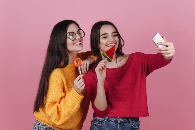 Two smiling girls take selfie on their phones posing with lollipops Free Photo