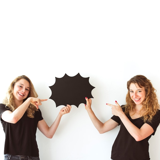 Two smiling sisters holding black speech bubble pointing fingers Free Photo