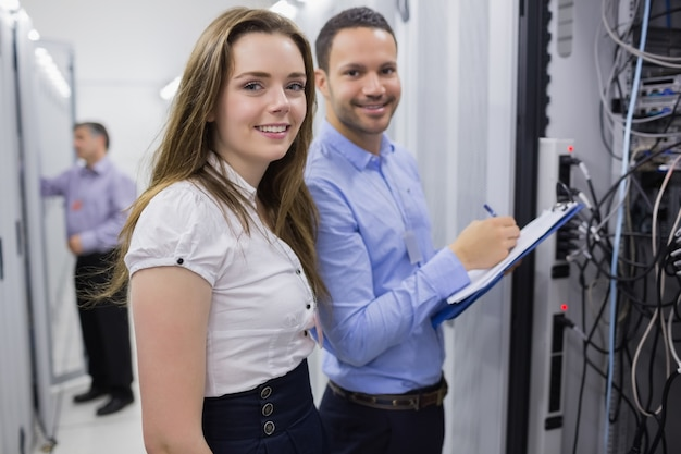 Two smiling  technicians checking the servers  Premium Photo