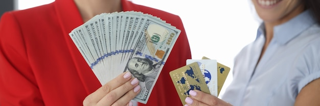 Две улыбающиеся женщины держат в руках сто долларовые банкноты и кредитные карты. удаленная работа фрилансером и зарабатывание денег в интернете концепция Premium Фотографии
