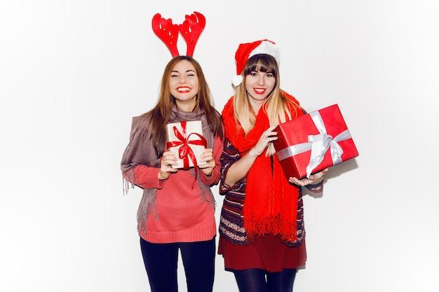 新年の贈り物を保持している笑顔の2人の女性。かわいい仮面舞踏会の帽子をかぶっています。率直な笑顔。気分を祝います。フラッシュポートレート。 無料写真
