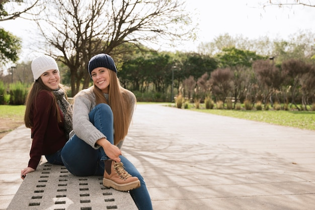 Two smiling women sitting on a bench Free Photo