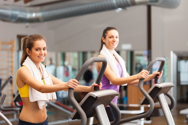 Two smiling women working out in a gym Premium Photo