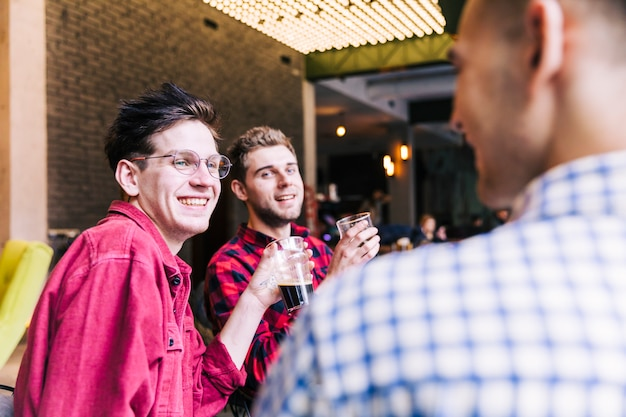 Two smiling young men holding beer glasses looking at their friend Free Photo