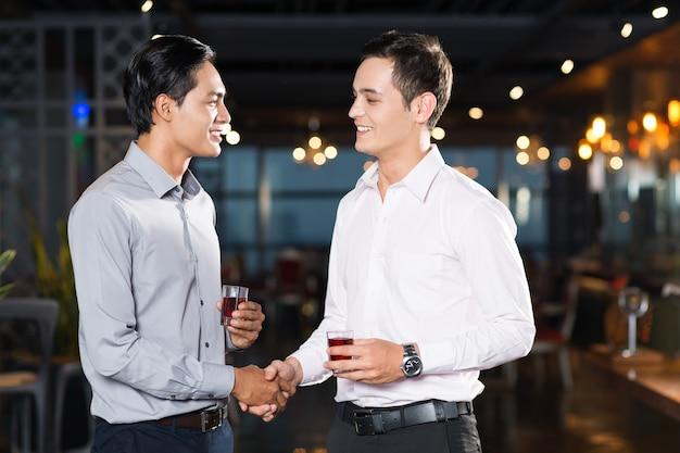 Discuter avec des inconnus ou leur sourire dans la rue ou ailleurs fait le plus grand bien ! Two-smiling-young-men-shaking-hands-party_1262-1657