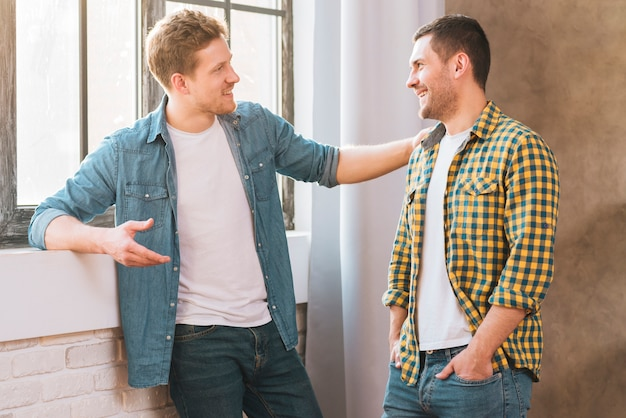 Two smiling young men talking to each other Free Photo