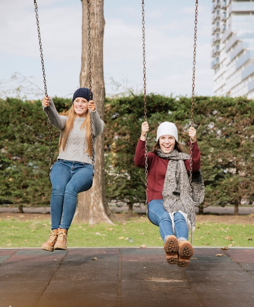 Two smiling young women on swings Free Photo