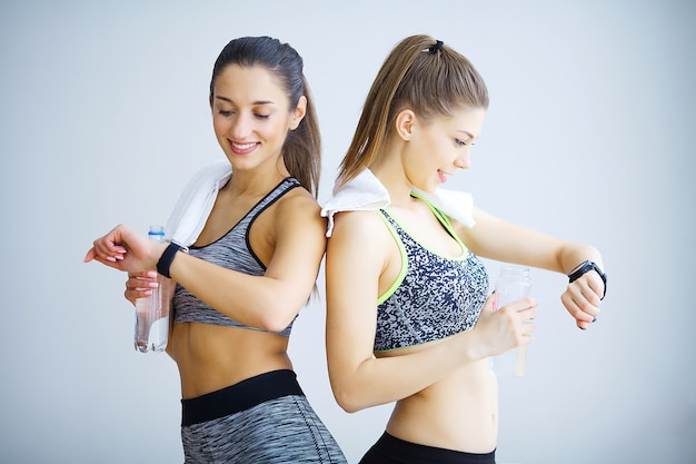 Two sporty girls looking something on smart watch in gym. Premium Photo