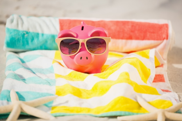 Two starfish and piggy bank with sunglasses on sand Free Photo