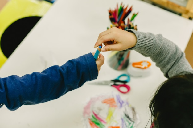 Two students share pencils in a nursery school Premium Photo