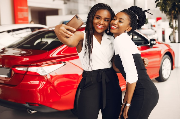 Two stylish black women in a car salon Free Photo