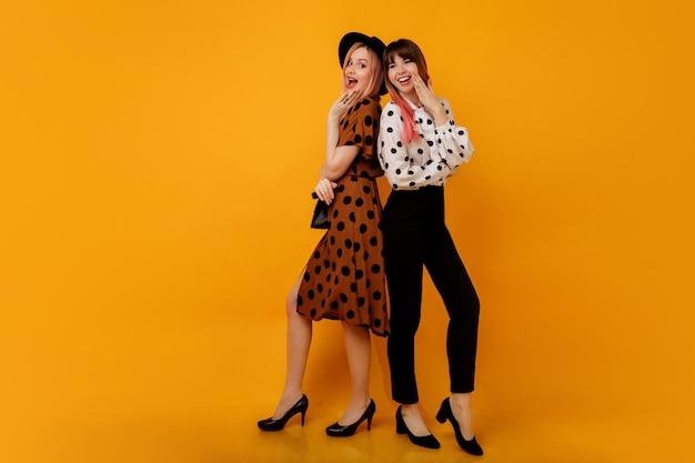 Две стильные элегантные женщины в платьях позируют на желтой стене Бесплатные Фотографии