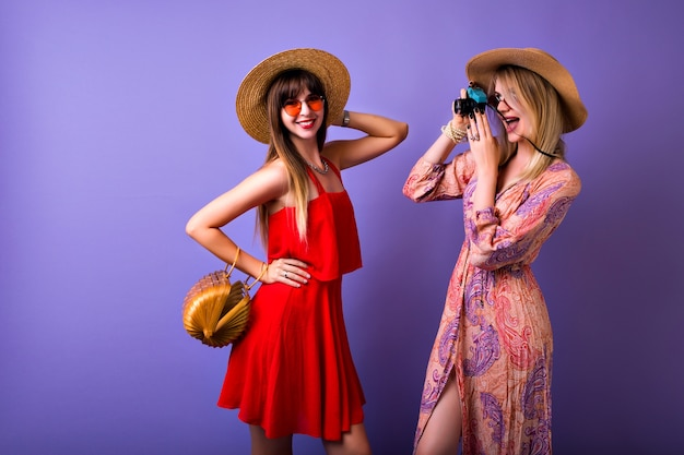 Two stylish hipster girls having fun together, vintage boho dress hats and accessories, blonde woman making pictures of her best friend, Free Photo