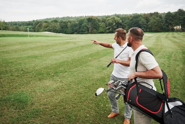 클럽과 가방을 들고 골프 코스를 걷고 두 세련된 남자 프리미엄 사진