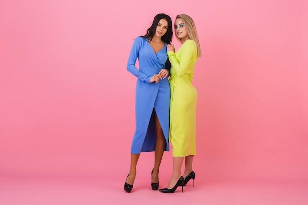 Две стильные сексуальные привлекательные женщины позируют в полный рост на розовой стене в стильных красочных платьях синего и желтого цвета, весенняя мода Бесплатные Фотографии