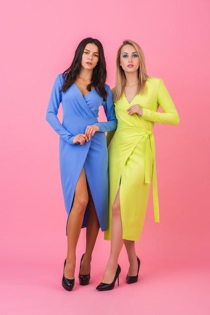 Две стильные сексуальные привлекательные женщины позируют в полный рост на розовой стене в стильных красочных платьях синего и желтого цвета, тренд летней моды Бесплатные Фотографии