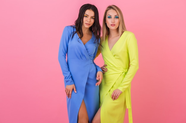 Две стильные сексуальные привлекательные женщины позируют на розовой стене в стильных красочных платьях синего и желтого цвета, тренд летней моды Бесплатные Фотографии