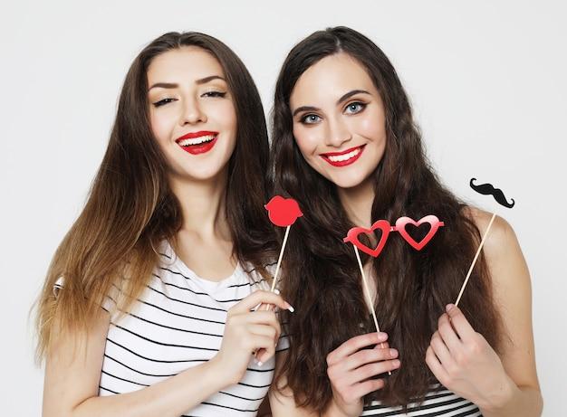 Две стильные сексуальные девушки лучшие друзья держат бумажные палочки для вечеринок Premium Фотографии