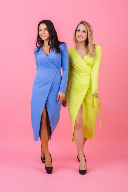 Две стильные сексуальные улыбающиеся привлекательные блондинки и брюнетки позируют на розовой стене в стильных красочных платьях синего и желтого цвета, тренд летней моды Бесплатные Фотографии