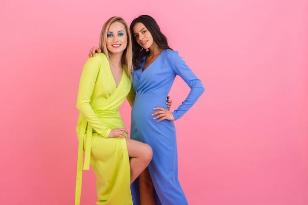 Две стильные сексуальные улыбающиеся привлекательные женщины позируют на розовой стене в стильных красочных платьях синего и желтого цвета, тренд летней моды Бесплатные Фотографии
