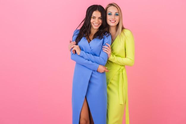 Две стильные улыбающиеся привлекательные подруги позируют на розовой стене в стильных красочных платьях синего и желтого цвета, весенняя мода Бесплатные Фотографии