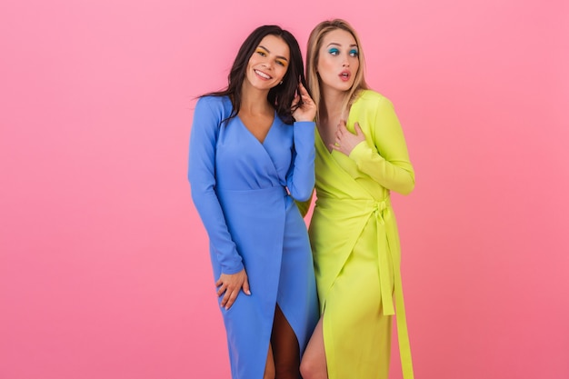 Two stylish smiling attractive women friends posing on pink wall in stylish colorful dresses of blue and yellow color, spring fashion trend Free Photo