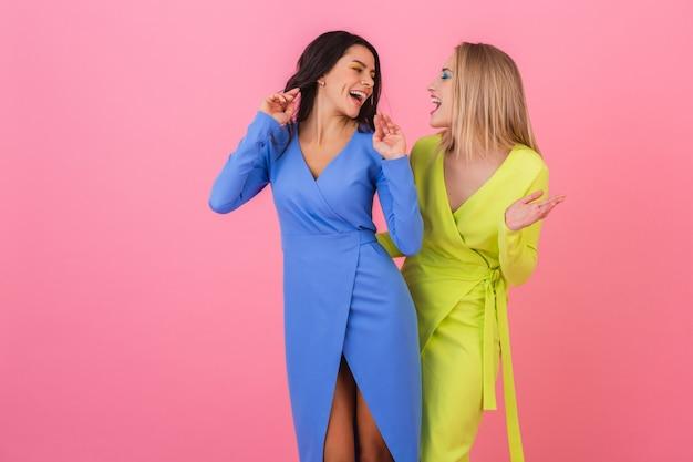 Две стильные улыбающиеся привлекательные женщины с удовольствием позируют на розовой стене в стильных красочных платьях синего и желтого цвета, весенняя мода Бесплатные Фотографии