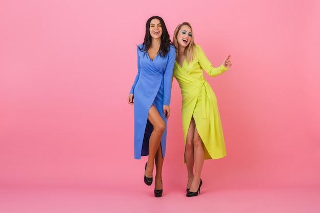 Две стильные улыбающиеся привлекательные женщины в ярких платьях с удовольствием позируют в полный рост на розовой стене, одежда синего и желтого цветов, тренд летней моды Бесплатные Фотографии