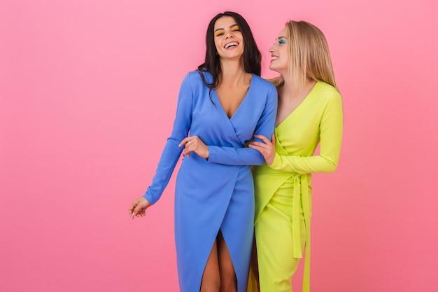 Две стильные улыбающиеся привлекательные женщины в ярких платьях весело позируют на розовой стене, в одежде синего и желтого цветов, тренд летней моды Бесплатные Фотографии