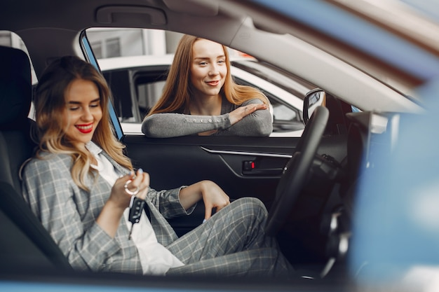 Two stylish women in a car salon Free Photo