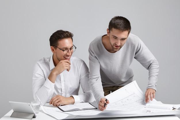 넓은 조명 사무실에서 청사진을 공부하는 두 명의 성공적인 전문 남성 생성자 무료 사진