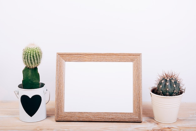 Two succulent plants on sides of empty photo frame on wooden desk Free Photo