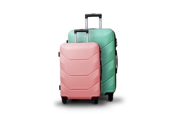 2 чемодана на колесах на предпосылке изолированной белизной. концепция путешествия, поездка в отпуск, визит к родственникам. розовый и зеленый цвет Premium Фотографии