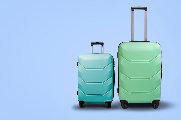 Two suitcases on wheels on a blue background. concept of travel, a vacation trip, a visit to relatives. pink and green color Premium Photo