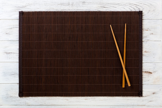 Two sushi chopsticks with empty bamboo mat or wood plate on white wooden Premium Photo