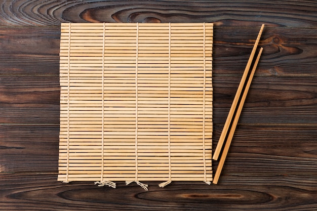 Two sushi chopsticks with empty brown bamboo mat Premium Photo