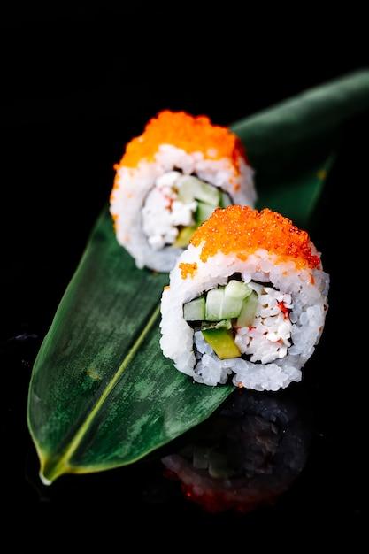 黒スペースの緑の葉の上に2本の寿司があります。 無料写真