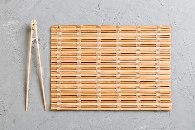 Two sushi training sticks with empty bamboo mat or wood plate on stone Premium Photo